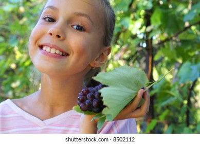 Smiling preteen girl with grapes on grapevine background