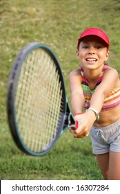 Smiling preteen girl playing tennis
