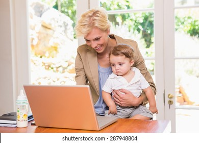 Smiling pretty blonde woman using laptop with his son in the office