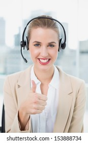 Smiling pretty call center agent in bright office wearing headset giving thumbs up