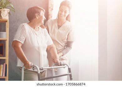 Lächeln hübsche Pfleger und alte Dame mit Walker im Pflegeheim