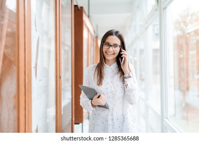 Smiling pretty Caucasian collage girl with brown hair and eyeglasses holding tablet and using smart phone while standing next to noticeboard in university hall.