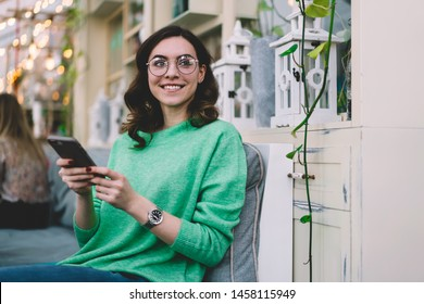 Smiling pretty curly haired young girl in green sweater, round glasses and wrist watch sitting with gray smartphone in cafe