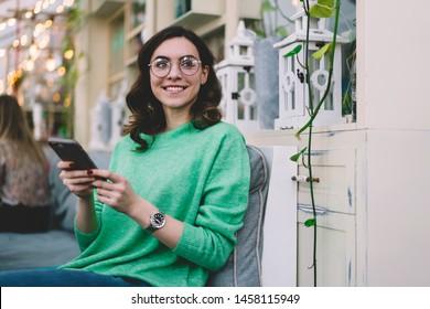 Lächelnd hübsch lockiges, junges Mädchen in grünem Pullover, runde Gläser und Armbanduhr sitzend mit grauem Smartphone im Café