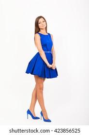 Smiling pretty girl in blue dress, studio full length portrait