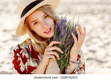 Smiling pretty girl with candid smile  in straw hat posing on sunny beach near ocean with bouquet of flowers. Close up portrait.  Natural make up.  Sunny spring day.