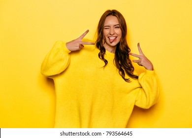 Smiling pretty girl with curly hair winking, showing a tongue, peace gesture. On yellow background.