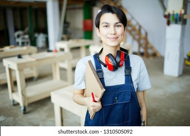 Smiling pretty girl with ear protectors on neck wearing uniform standing in workshop and holding pencil and sketchpad while looking at camera, she learning about carpentry