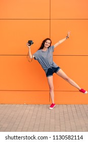 Smiling pretty girl posing on one leg with vintage camera in front of orange wall