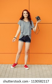 Smiling pretty girl posing with vintage camera in front of orange wall