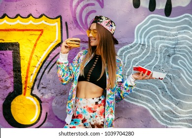 Smiling pretty girl ready to eat a hamburger. Dressed in bright clothes, fashion cap, in sunglasses, standing on the wall background with a graffiti in purple and yellow tones. Outdoors.