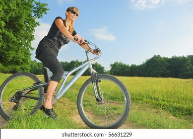 smiling pretty girl riding a bike in green environment