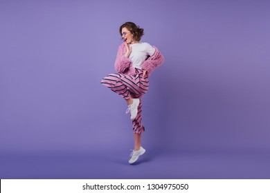 Smiling pretty girl with wavy hairstyle standing on one leg on purple background. Studio portrait of cheerful brunette female model dancing in white sneakers.