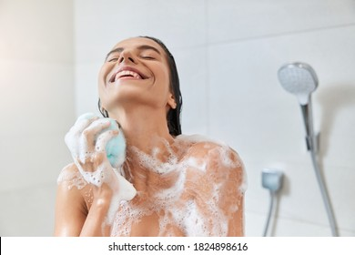 Smiling pretty lady with foam on her skin using exfoliating bath sponge while taking shower at home