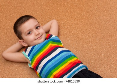 A smiling pretty little boy in bright striped shirt lying on the floor
