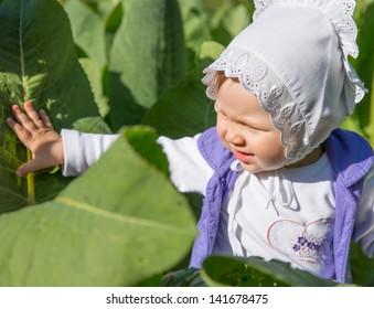 Smiling pretty little child girl in leaves of burdock in park