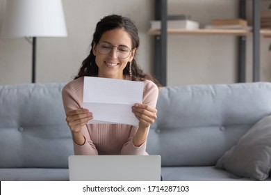 Smiling pretty millennial female student in glasses sitting on sofa, reading paper university admission notification. Happy pleasant young woman wearing eyeglasses reading good news letter at home.