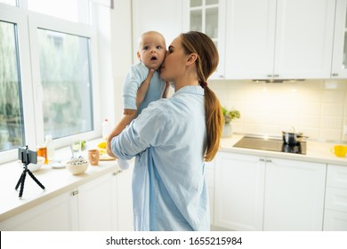 Smiling pretty mother holding her little kid while standing at home stock photo