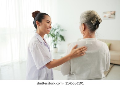 Smiling pretty nurse talking to senior woman at home