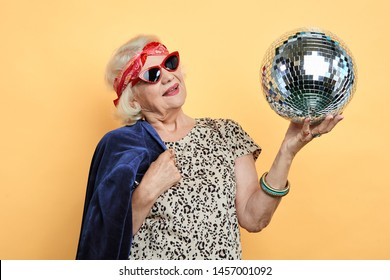 smiling pretty old woman looking at the ball, old lady remember her youth. isolated yellow background. studio shot