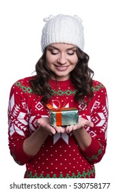 Smiling pretty sexy young woman wearing colorful knitted sweater with christmas ornament and hat, holding christmas gift. Isolated on white background. Winter clothes concept.