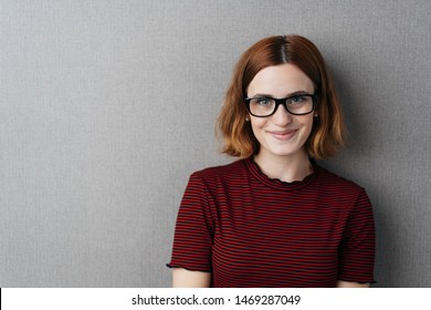 Smiling pretty studious young woman in heavy rimmed glasses posing over grey with copy space looking at camera with a beaming smile