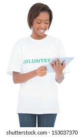 Smiling pretty volunteer looking at her tablet pc on white background