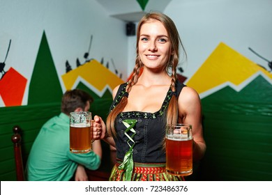Smiling pretty waitress in german octoberfest suit posing with two beer glasses. Happy couple on the background.