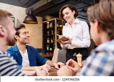 Smiling pretty waitress with short hair wearing white blouse standing at table with guests and making notes in sketchpad while taking order in restaurant, cheerful guys flirting with her