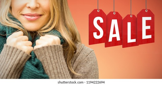 Smiling pretty woman holding her scarf against abstract yellow background