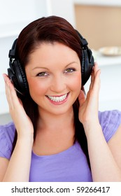 Smiling pretty woman listen to music with headphones looking at the camera at home