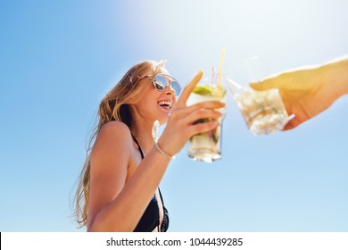 Smiling pretty woman with long hair in swimsuit and sunglasses, drinking a cocktail, toasting, celebrating something with friend, spending vacation on the beach, at sunny day. Bottom view