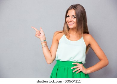 Smiling pretty woman pointing finger away over gray background. Looking at camera