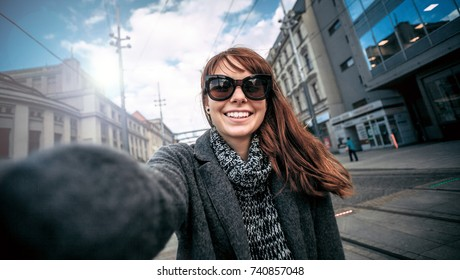 Smiling pretty woman selfie portrait at the city street