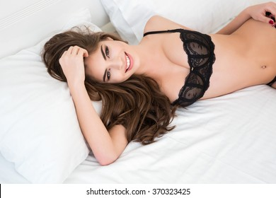 Smiling pretty woman in sexy lingerie lying on the bed and looking at camera