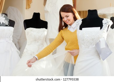 Smiling pretty woman shopping for wedding outfit in bridal boutique
