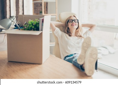 Smiling pretty woman sitting in armchair with her feet on the table and feeling happiness because of new position at work.