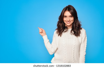 Smiling pretty woman in white sweater showing with finger away on bright blue background