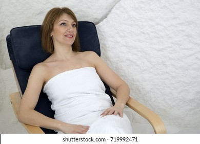 Smiling Pretty Woman In A White Towel Relaxing In The Salt Room