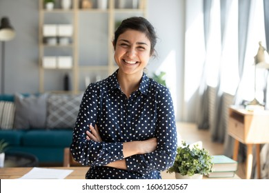 Smiling pretty young adult indian woman looking at camera posing at modern home arms crossed, cheerful happy ethnic girl student self employed lady laughing enjoying distance job education, portrait - Shutterstock ID 1606120567