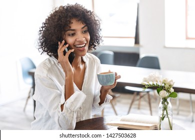 Smiling pretty young african woman relaxing at the cafe indoors, using mobile phone, talking