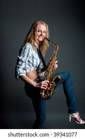 smiling pretty young blonde gilr with saxophone having fun with lifted leg isolated over black
