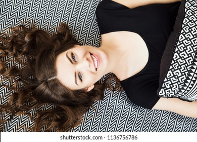 Smiling pretty young girl with long wavy hair in a black dress laying on the bed. Stylish beautiful woman with bright smile and pillow in hands.