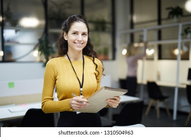 Smiling pretty young lady with badge on neck standing in modern open space office and holding sketchpad while looking at camera