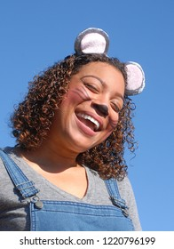 Smiling, pretty young woman with curly hair and of mixed race dressed in a mouse costume smiling at the viewer on a sunny day with a blue sky.