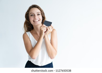 Smiling pretty young woman holding plastic card with both hands. Lady looking at camera. Cashless payment concept. Isolated front view on white background.