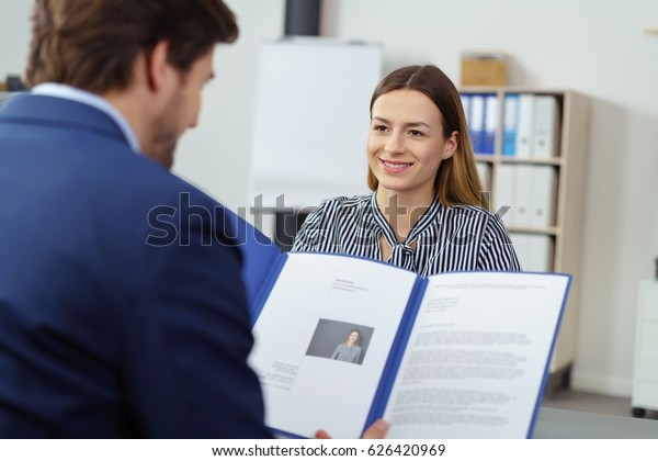 Smiling pretty young woman in a job interview watching as the personnel manager reads her CV in a blue file