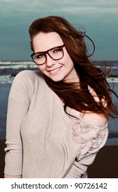 Smiling pretty young woman with long brown hair wearing glasses on the beach