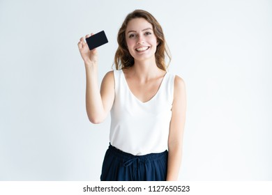 Smiling pretty young woman showing blank plastic card. Lady looking at camera. Banking concept. Isolated front view on white background.