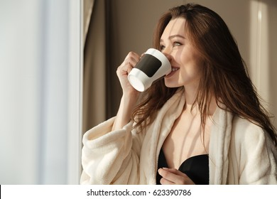 Smiling pretty young woman standing near the window and drinking coffee at home